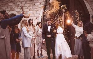 Wedding guests throw rice and flowers at a newly-wedded couple as they exit the church